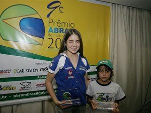Foto: Stefany Serrão (FOX) e Guilherme Costa (ASW) são premiados pela ABRAM