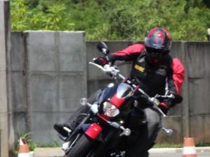 Corpo inclinando junto com a inclinação da moto; curvas abertas em médias velocidades