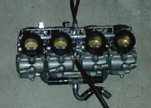 Grupo de quatro carburadores com sistema de acionamento do acelerador combinado, permite ajuste individual de cada borboleta