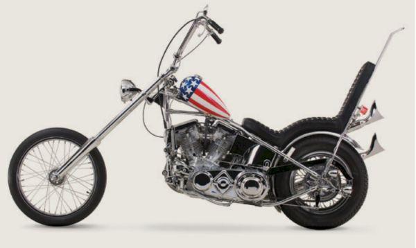 """O filme de 1969, """"Easy Rider"""", estrelado por Peter Fonda e Dennis Hopper, celebrizou a Imagem da Harley-Davidson no cinema com esse modelo """"Capitão América"""" chopper criado a partir de uma H&D FLH políce. Como o Modelo original foi destruído no Filme, para a comemoração dos 30 anos da marca, Peter Fonda ajudou a construir uma réplica que ocupa lugar de destaque no museu H&D"""