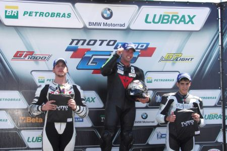 Pódio da GP Light, com Andreghetto recebendo seu capacete Bell, na companhia de Iatauro e Barros