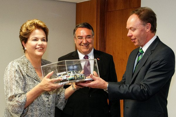 Ian Robertson presenteia a presidente Dilma Roussef com uma réplica miniatura de um carro BMW; o feliz governador de Santa Catarina, Raimundo Colombo, observa