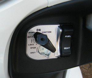 Botão para abrir o assento e o tanque de combustível no painel