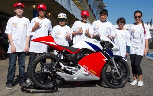 Garotada tendo contato com a moto do Honda Júnior Cup