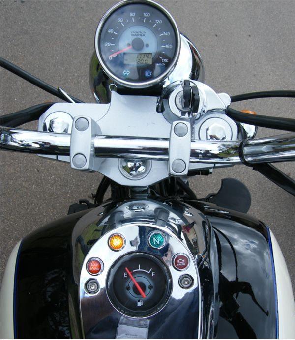 Instrumentação dividida entre o conjunto do velocímetro junto à direção e o painel sobre o tanque