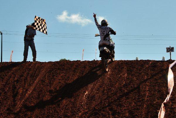 Balbi Jr recebendo a bandeira quadriculada que confirma sua liderança no Brasileiro de Motocross