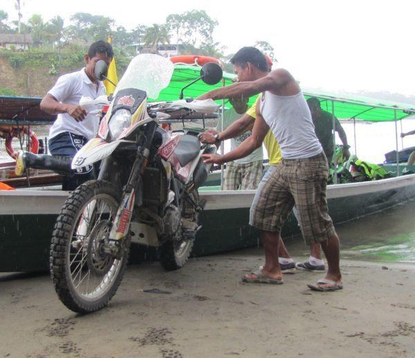 As motos vão carregadas no barco, para cumprir parte do trajeto no rio