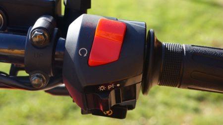 No punho direito consta além do botão de partida, uma chave para lanterna e farol e o interruptor do motor