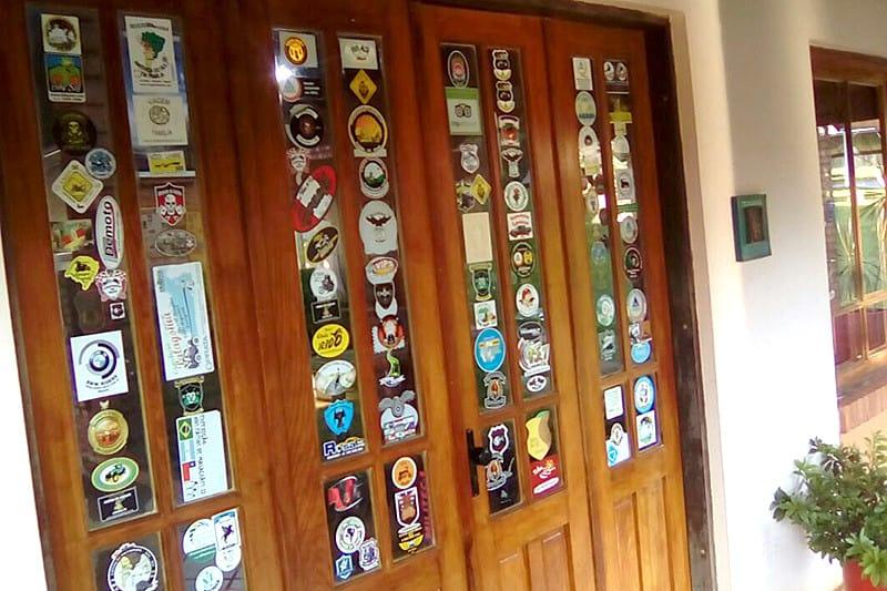 Pousada recebe muitos motociclistas, e eles deixam adesivos de suas expedições e motoclubes em janelas e portas