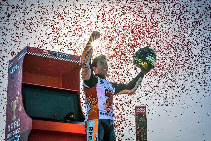 Assim que venceu a corrida, Márquez foi até uma espécie de fliperama (à esquerda) montado no autódromo, jogou uma partida de video-game por alguns segundos e, ao vencê-la, desbloqueou o 'nível 7', ganhando o capacete de World Champion (na sua mão direita) como recompensa. Criativo