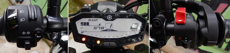 Comandos e painel: no punho esquerdo, um detalhe inútil; no punho direito, corta-corrente e botão de partida juntos; no meio, o painel digital completo e funcional