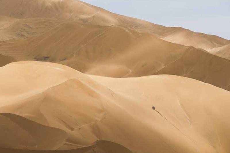 Sim, aquele ponto é um piloto desafiando a imensidão do deserto peruano com uma motocicleta - Foto: Dakar/DPPI